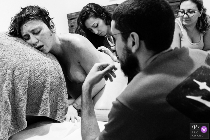 A woman going through labor is exhausted, and is surrounded by her family   Sao Paulo Birth Photography