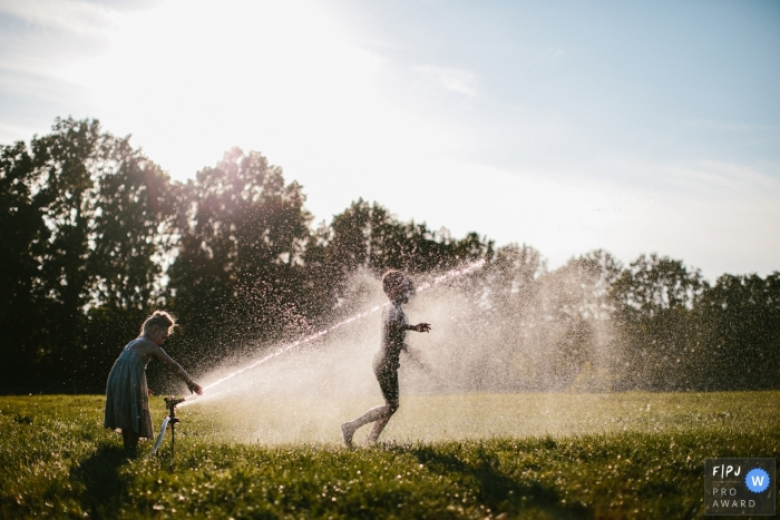 Netherlands Family Photography | A couple of children enjoy the first warm days of the year by running through thet sprinklers