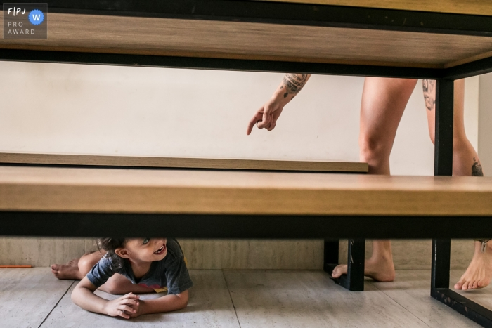 Minas Gerais family photography of a daughter hiding from mother under the table.