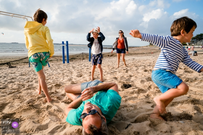 A dad rolls in the sand as the children run around during a family photo shoot