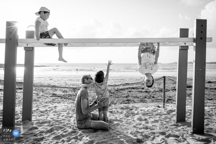 A family plays on monkey bars at the beach | Nantes Family Photo Session