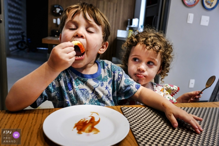 A young boy enjoys a snack at the table as his sibling watches intently   Minas Gerais family and kids photography