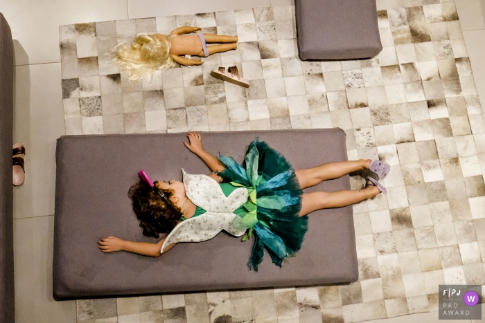 Image of a young girl dressed as a fairy takes a well deserved nap on a mattress and her doll mimics her   Brazil family photo