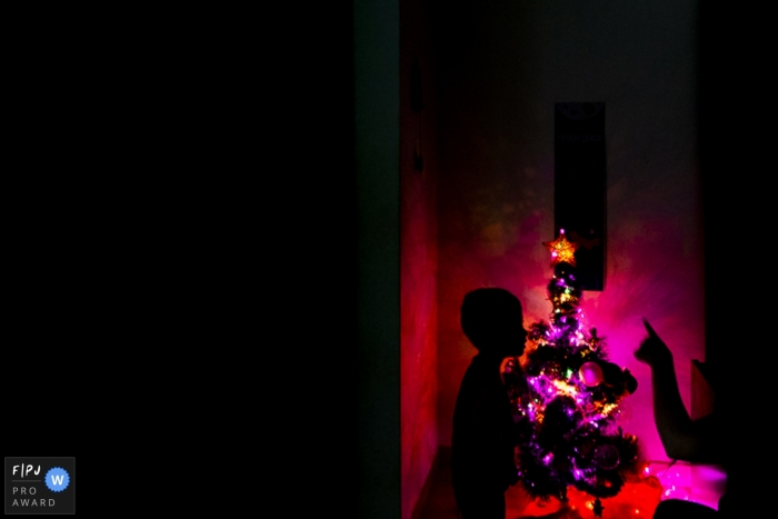 The family turning on the Christmas tree in the dark. The mother is pointing her finger towards the star on the tree to show her son | Arapongas family holiday photographer