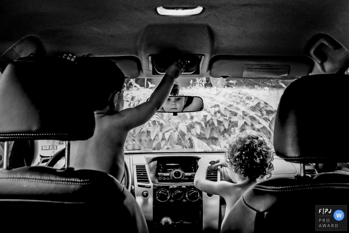 Two young men playing in the front seats of the auto having a good ole time playing | Minas Gerais documentary family photographer