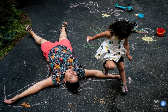 New Hampshire family photo of a little girl expertly jumping over mom laying on driveway traced out with chalk.