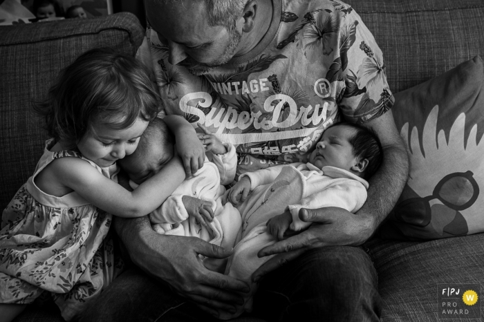While daddy is carrying the newborn twins, his little girl is giving one of the babies a huge hug | Auvergne Rhone Alpes family photographer