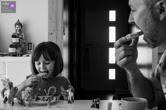 A child having breakfast with  her father   Savoie Family Photographer
