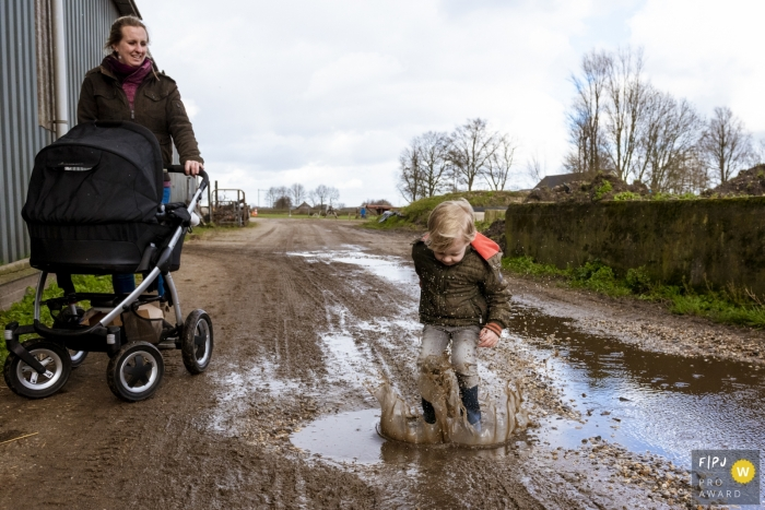 Noord Holland family photo shoot of a mom with stroller watching as her son jumps in puddles.