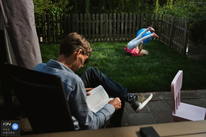 Young child plays on the grass in the yard as dad takes in a good book | Amsterdam Family Photographer