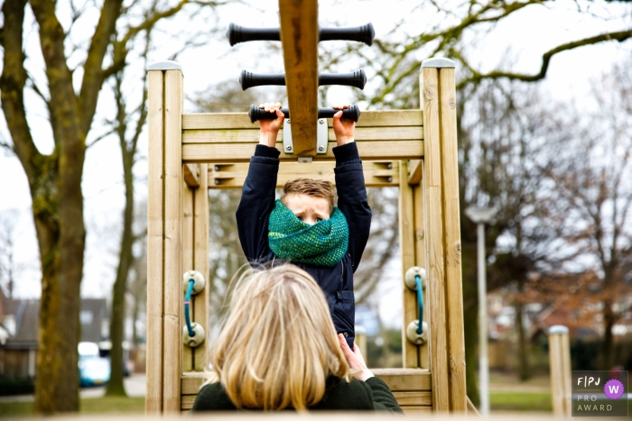 Boy plays on a playground with mom ready to catch him from the monkey bars | Netherlands children photographer