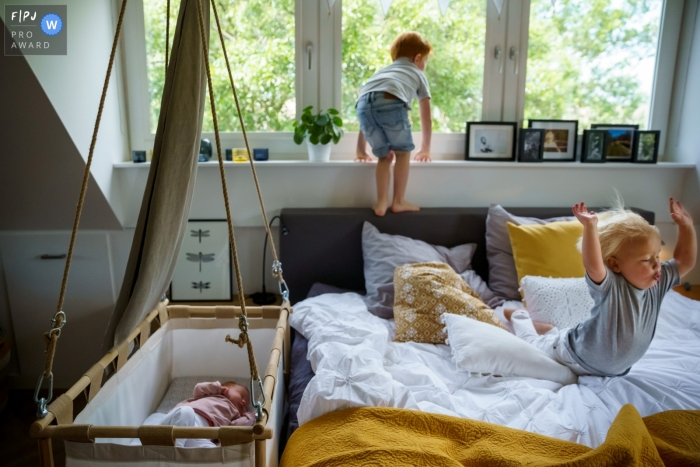 Two boys jump on a big bed as a young sibling sleeps soundly in a bassinet next to the bed | Overjssel Family Photography