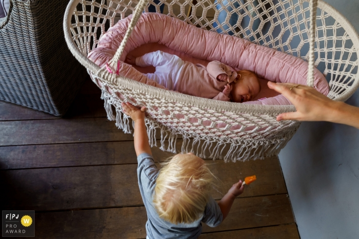 Mom holds a hanging bassinet as a young sibling tries to swing his sister