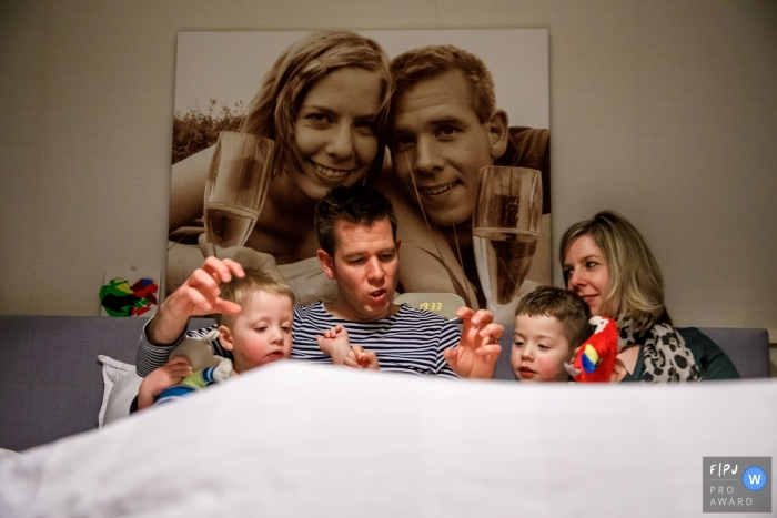 Family sits for a bed time story on a  sofa that displays a portrait of mom and dad on their wedding day | Netherlands family photographer