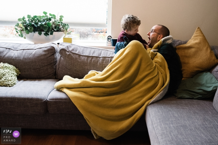 Father and son playing on a sofa, having a great time together | Eindhoven family photo session