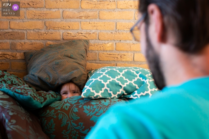 A young child hids amongst pillows, peeking out at dad | Breda Family Photographer
