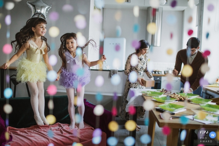 Birthday party scene of girls jumping in fairy costumes and the parents working at the snack table | Russia Birthday Party Photographer