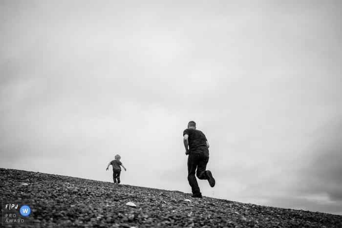 dad and kid race up hill | Washington documentary family photography