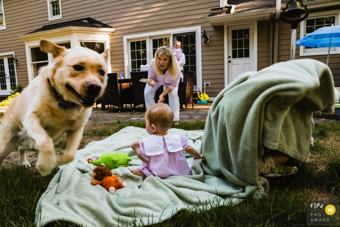 An image of backyard mayhem as dog runs off taking baby toys and big brother plays under blanket