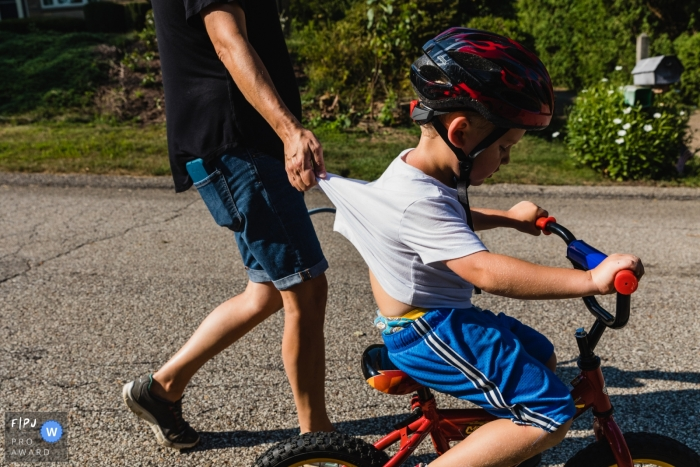 mom holds little boy's shirt as he rides his bike down the street during a family photo shoot in Pennsylvania