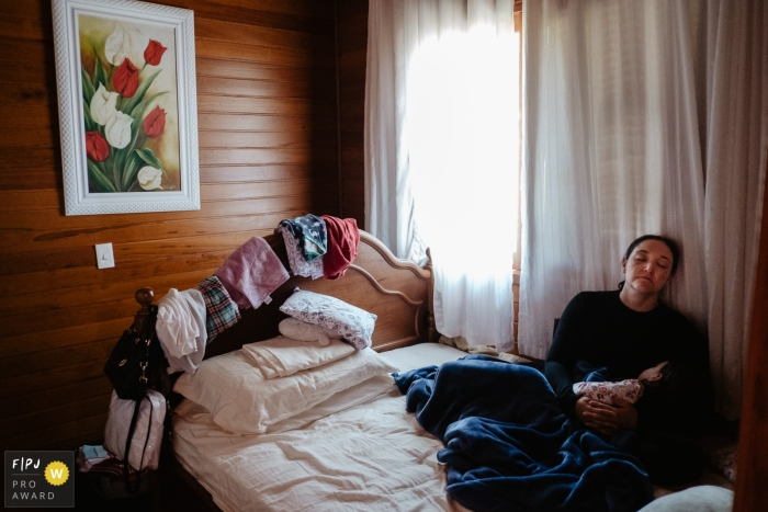 Mother, tired, with her daughter sleeping in a bedroom, with window light, on a Saturday afternoon. Clothes at the bottom, on top of the bed and headboard during a family photojournalism shoot in Brazil.