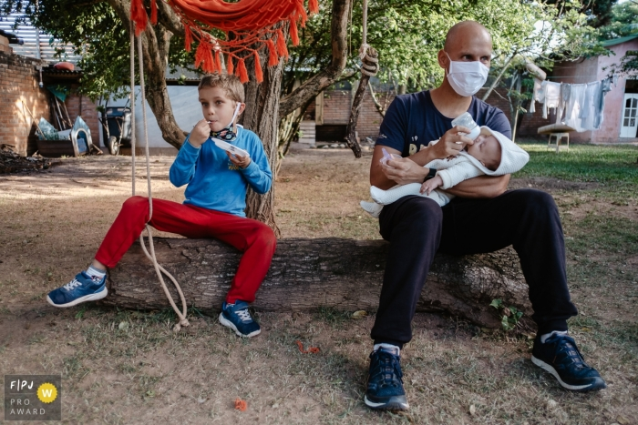 Father in a protective mask, giving a bottle to his youngest son, while the older and birthday boy eats his cake. The two are sitting in a home garden in Brazil.