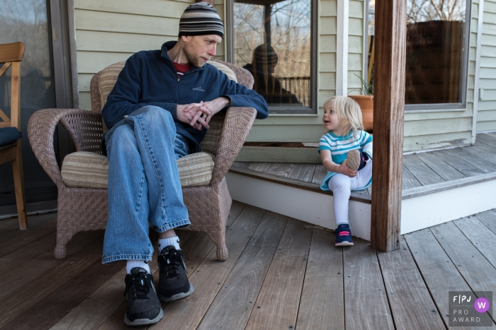 Connecticut family photo session of dad and daughter sharing a moment on the porch.