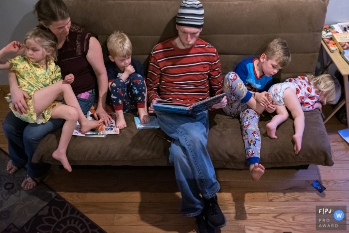 Connecticut family sitting on a sofa as dad reads a book.