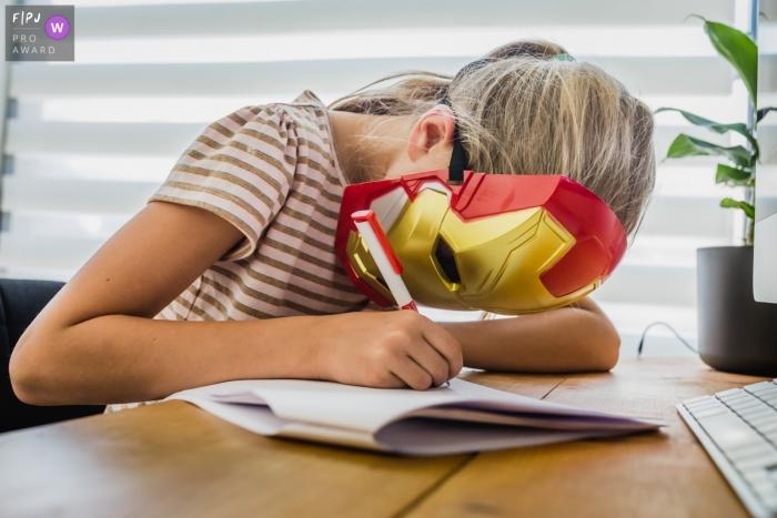Limburg Family Photographer   Girl works on her homework while wearing an Iron Man mask