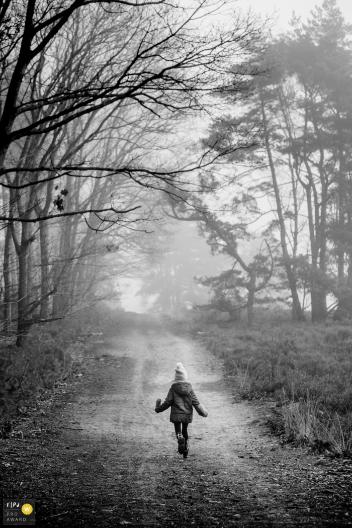 Limburg Family Photo of a girl taking a winter walk on a tree-lined road