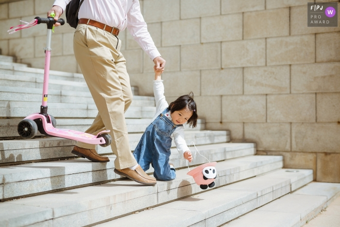 Shanxi Family Image of little girl accidentally falling down the stairs trying to catch her hat