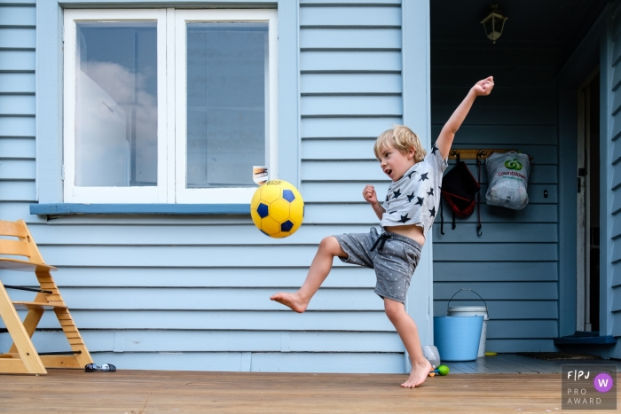 Berlin Family Photo of boy playing soccer in the backyard