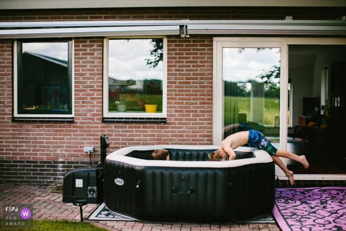 Drenthe Documentary Family picture of a boy taking a dive in the jacuzzi on sunday-morning