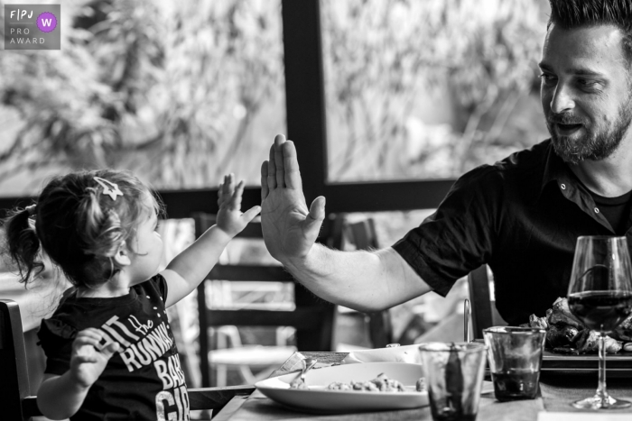 Essex Documentary Family Session | little girl giver her dad a high five during a restaurant meal