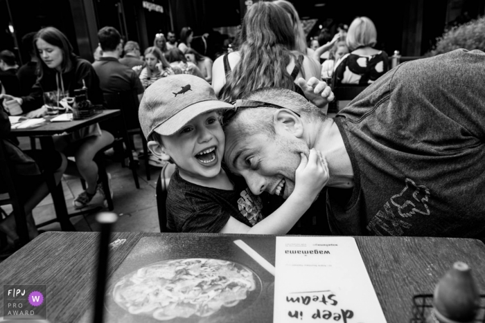 Essex Documentary Family Photography | Boy pinches his father's face at a restaurant