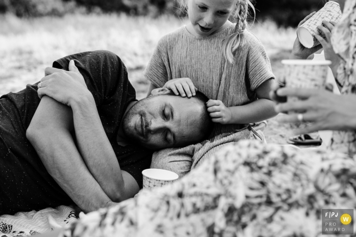Netherlands Documentary Family Session | young girl holds her father's head in her lap as he rests