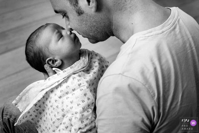 Paris family photo of infant being held by dad going nose to nose