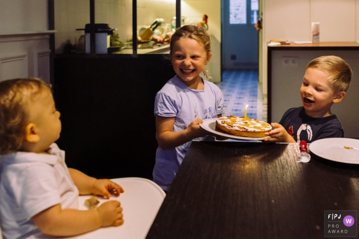 Paris Documentary Family photo of siblings arriving at the table with a cake and one single candle to their younger brother