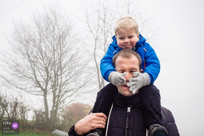 Germany Documentary Family photo of young boy sitting on his father's shoulders having fun