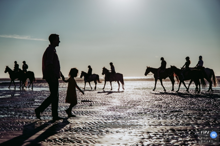 East Flanders family image of father and daughter on the beach, silhouetted with horseback riders in the background