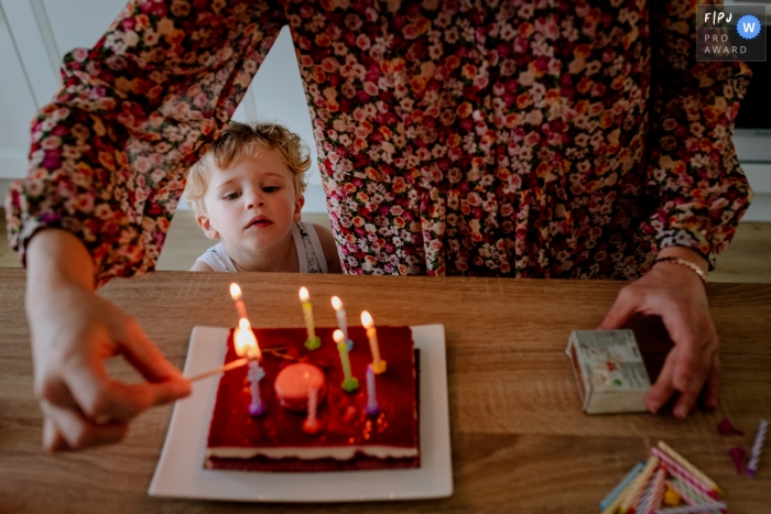 Occitanie Documentary Family Photography | boy watches the birthday cake and the candles are lit