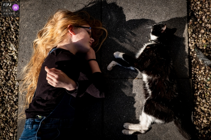 Netherlands Documentary Family photo of a girl and cat lying on the sidewalk