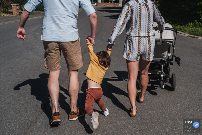 Flanders Documentary Family Photography | Mom and dad 'walking' with their son, against his will