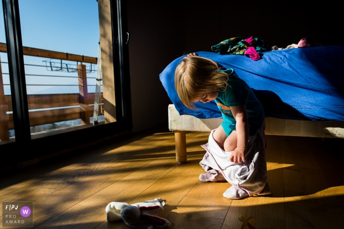 Savoie Family photography of a little girl tries to take off her pajamas without help.