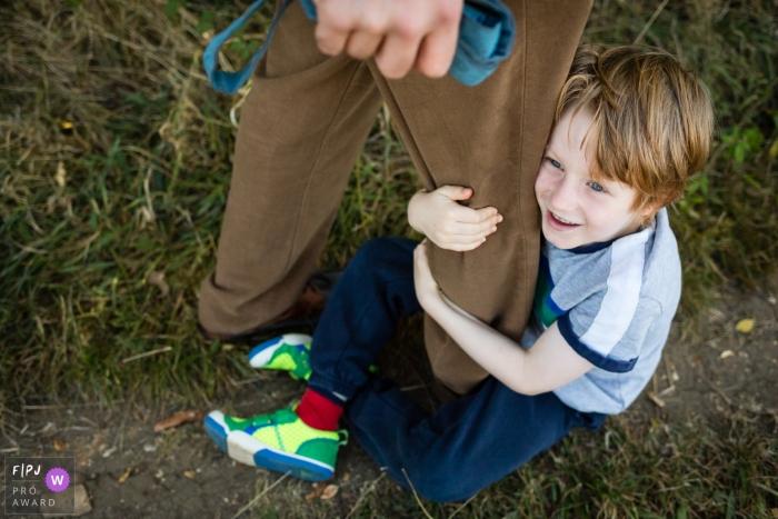 Cambridgeshire Family Photography of boy clinging to dad's leg on walk