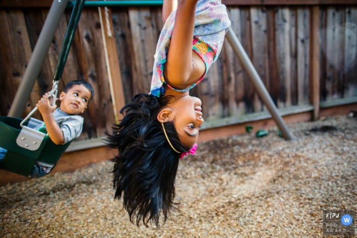 San Francisco Documentary Family Photo of two siblings playing on a swingset