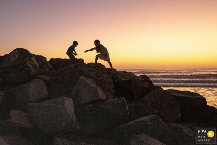 Ventura Documentary Family Photo   a silhouette image shows a girl reaching a hand out to help her brother navigate the rocks at the beach during sunset