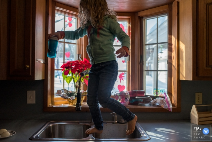 Connecticut Documentary Family photo of Young girl running across the counters making breakfast