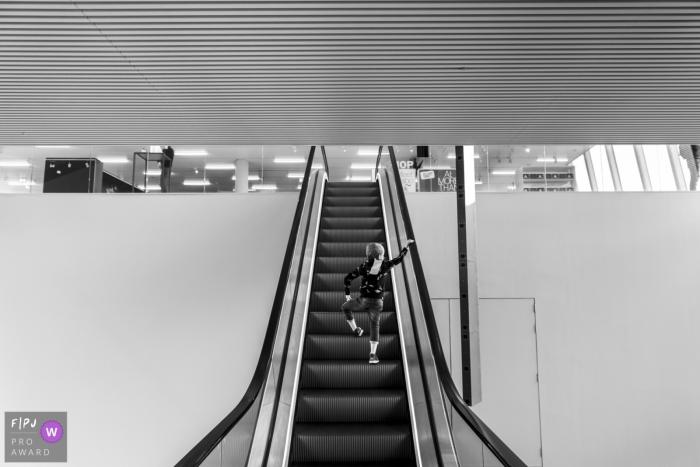 Noord Holland Family Photo | boy climbing up an escalator