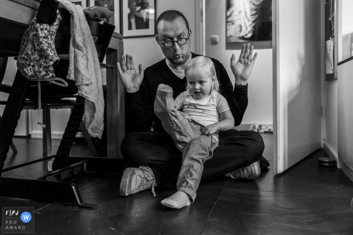 Noord Holland Family Photographer | young girl sitting in her father's lap is insistent upon getting dressed all by herself
